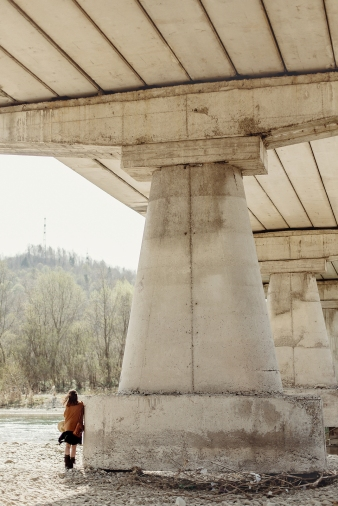 Stylish Boho Woman Posing At River Under Stone Bridge, Back View