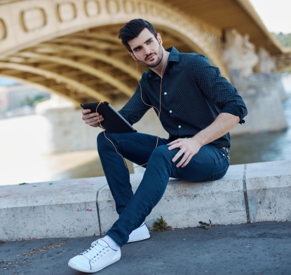 Handsome young man sitting under bridge, using tablet computer,
