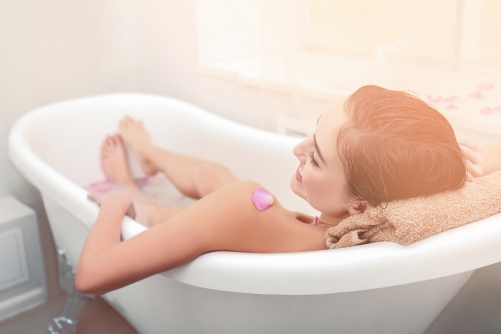 Young attractive woman relaxing in bath with foam and petals