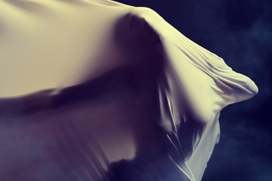 Art photo of a female silhouette breaking through the fabric. St