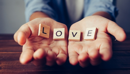 """The Word """"love"""" In Hands In Cupped Shape. Concepts Of Sharing, G"""