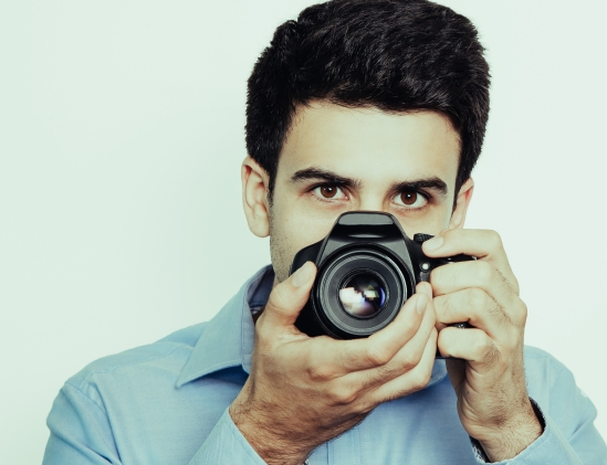 Portrait Of Male Photographer Working And Using Camera. Concentr
