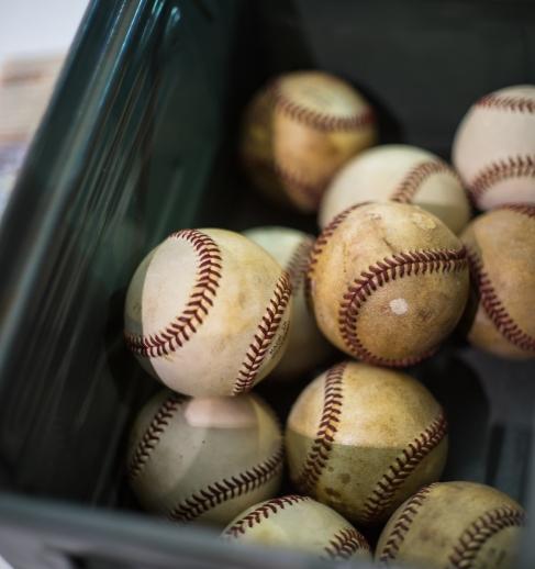 Several battered baseballs in a plastic box at flea market